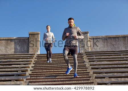 fitness, sport, people and lifestyle concept - couple running downstairs in city - stock photo