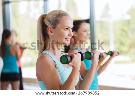 fitness, sport, people and lifestyle concept - group of women exercising with dumbbells in gym - stock photo