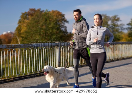 fitness, sport, people and lifestyle concept - happy couple with dog running outdoors - stock photo