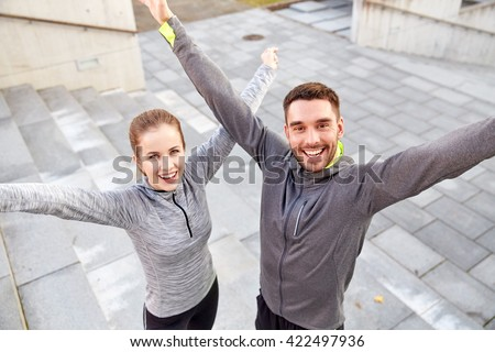 fitness, sport, people and lifestyle concept - happy smiling couple outdoors on city street - stock photo