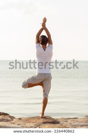 fitness, sport, people and lifestyle concept - young man making yoga exercises on beach from back - stock photo