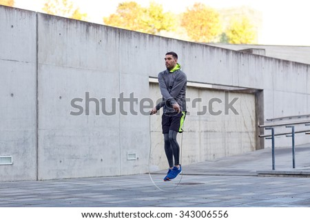 fitness, sport, people, exercising and lifestyle concept - man skipping with jump rope outdoors - stock photo