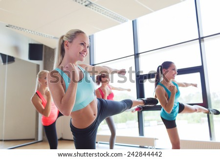 fitness, sport, people, martial arts and gym concept - group of women working out and standing in battle stance - stock photo
