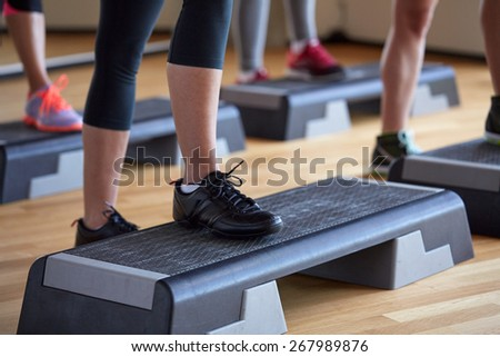 fitness, sport, people, step aerobics and lifestyle concept - close up of women legs exercising with steppers in gym - stock photo