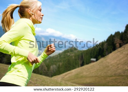 fitness, sport, people, technology and healthy lifestyle concept - happy young woman with earphones jogging or running  over mountains and blue sky background - stock photo