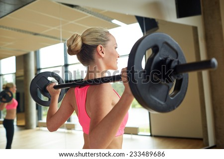 fitness, sport, powerlifting and people concept - sporty woman exercising with barbell in gym - stock photo