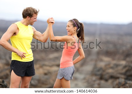 Fitness sport running couple celebrating cheerful and happy giving high five energetic and cheering. Runner couple having fun after trail cross-country running training. Asian woman, Caucasian man. - stock photo