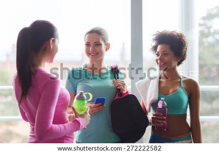 fitness, sport, training and lifestyle concept - group of happy women with bottles of water, smartphone and bag talking in gym - stock photo