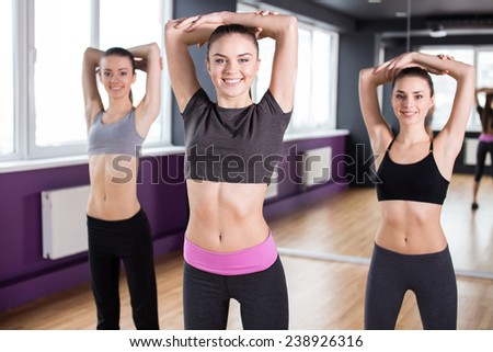 Fitness, sport, training and lifestyle concept. Group of smiling women are stretching in gym. - stock photo