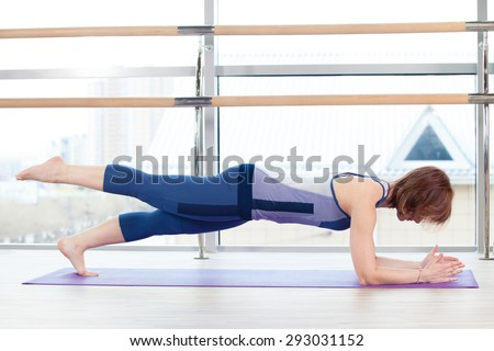 fitness, sport, training and lifestyle concept - smiling woman doing exercises on mat in gym - stock photo