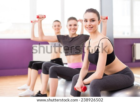 Fitness, sport, training and lifestyle concept - three smiling woman with exercise balls and dumbbells in gym. - stock photo