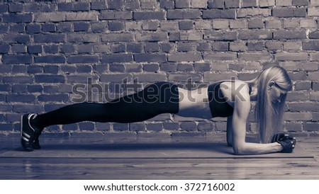 fitness, sport, training and lifestyle concept - woman doing plank exercises on mat at the gym. Toned black and white image. - stock photo