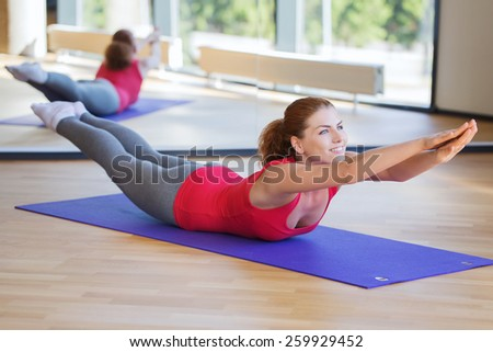 fitness, sport, training and people concept - smiling woman doing back extension exercise on mat in gym - stock photo