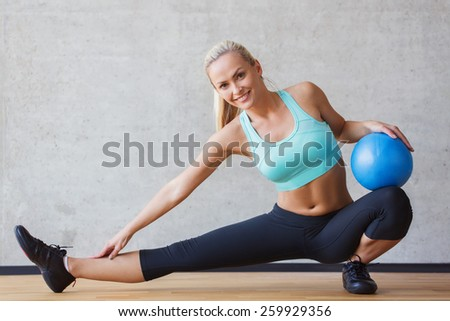 fitness, sport, training and people concept - smiling woman with exercise ball in gym - stock photo