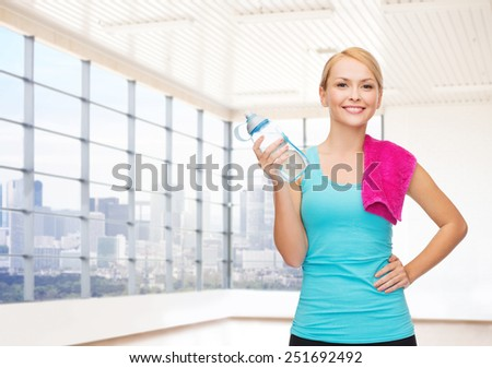 fitness, sport, training, drink and people concept - happy woman with bottle of water and towel over gym or home background - stock photo