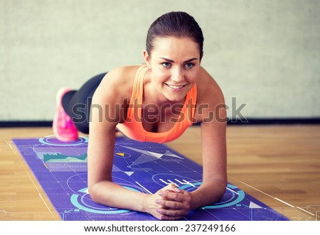 fitness, sport, training, future technology and lifestyle concept - smiling woman doing exercises on mat in gym over graph projection - stock photo
