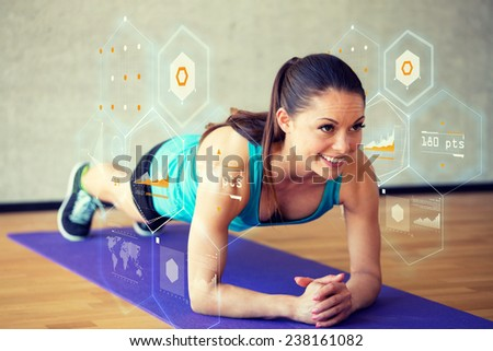 fitness, sport, training, future technology and lifestyle concept - smiling woman doing exercises on mat in gym and graph projection - stock photo