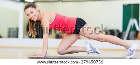 fitness, sport, training, gym and lifestyle concept - beautiful sporty woman doing exercise on the floor at gym - stock photo