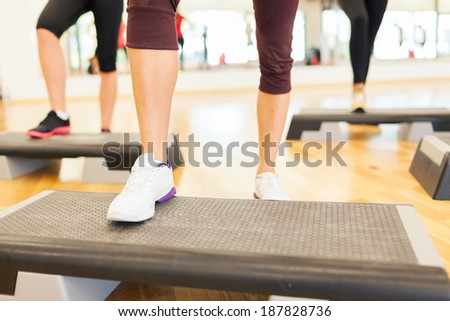 fitness, sport, training, gym and lifestyle concept - close up of women legs steping on step platform in gym - stock photo