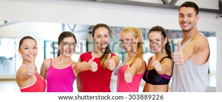 fitness, sport, training, gym and lifestyle concept - group of happy people in the gym showing thumbs up - stock photo