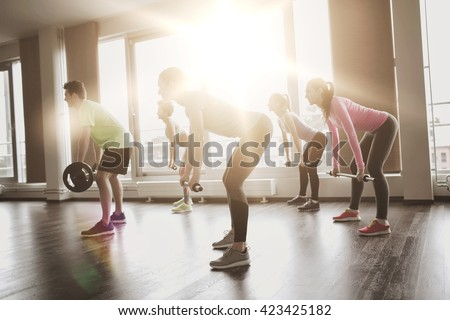 fitness, sport, training, gym and lifestyle concept - group of people exercising with barbell and bars in gym