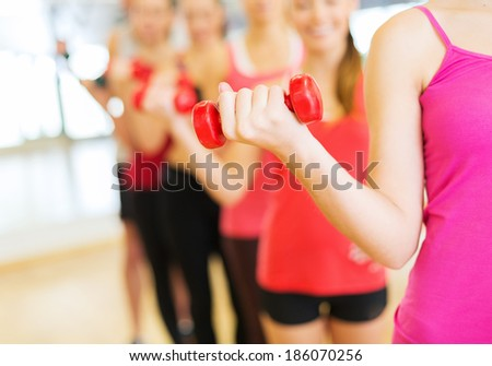 fitness, sport, training, gym and lifestyle concept - group of people working out with dumbbells in the gym - stock photo