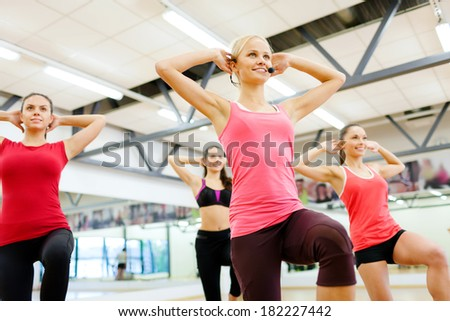 fitness, sport, training, gym and lifestyle concept - group of smiling female with trainer exercising in the gym - stock photo