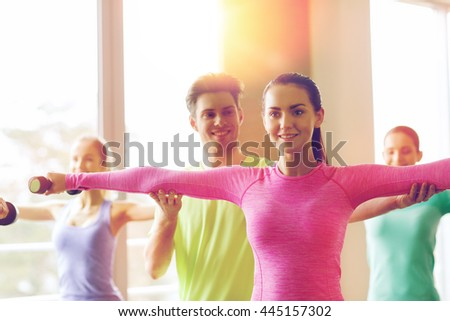 fitness, sport, training, gym and lifestyle concept - group of smiling people working out with dumbbells flexing muscles s in gym - stock photo