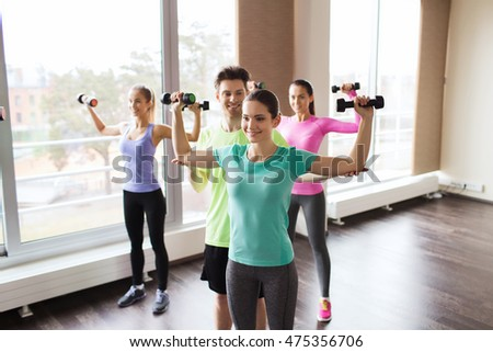 fitness, sport, training, gym and lifestyle concept - group of smiling people working out with dumbbells flexing muscles s in gym