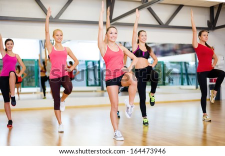 fitness, sport, training, gym and lifestyle concept - group of smiling women exercising in the gym - stock photo