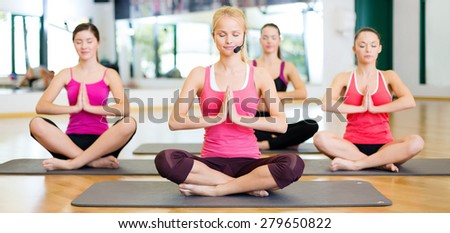 fitness, sport, training, gym and lifestyle concept - group of smiling women with trainer meditating in yoga pose - stock photo