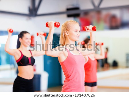 fitness, sport, training, gym and lifestyle concept - group of smiling women working out with dumbbells in the gym - stock photo