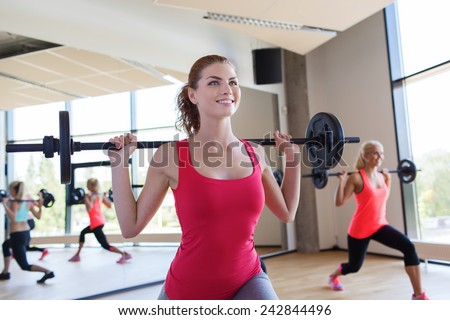 fitness, sport, training, gym and lifestyle concept - group of women excercising with bars in gym - stock photo