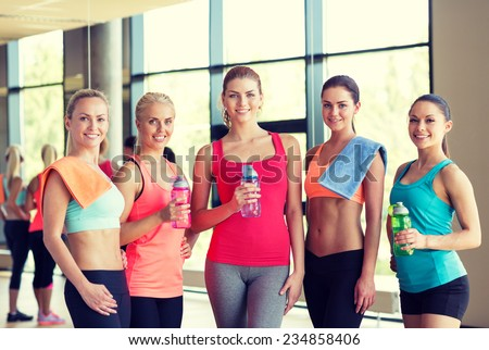 fitness, sport, training, gym and lifestyle concept - group of women with bottles of water in gym - stock photo