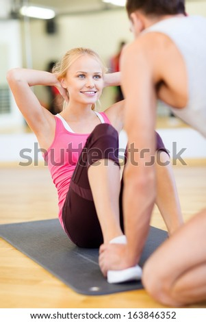 fitness, sport, training, gym and lifestyle concept - male trainer with woman doing sit ups - stock photo