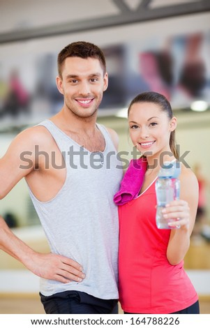fitness, sport, training, gym and lifestyle concept - smiling woman and man in the gym with water bottle and towel after class - stock photo