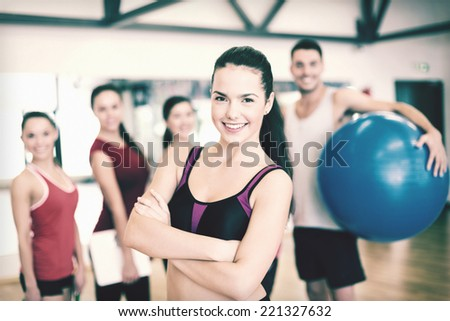fitness, sport, training, gym and lifestyle concept - smiling woman standing in front of the group of people in gym - stock photo