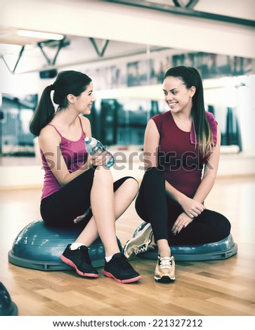 fitness, sport, training, gym and lifestyle concept - two smiling women sitting on the half ball and relaxing after class in the gym - stock photo