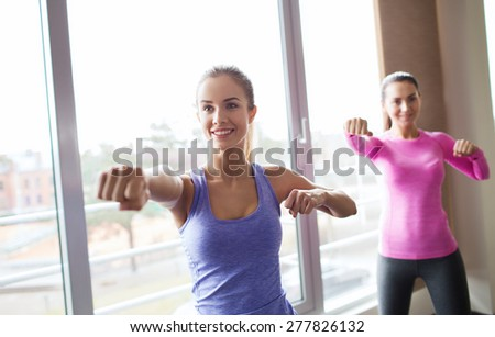 fitness, sport, training, gym and martial arts concept - group of happy women working out and fighting in gym - stock photo