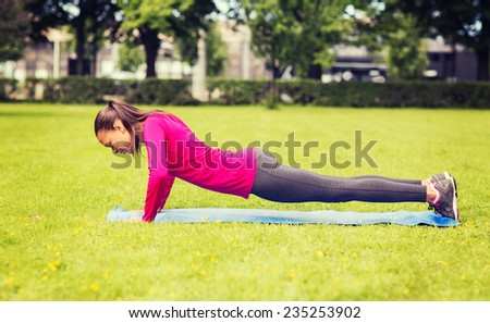 fitness, sport, training, park and lifestyle concept - smiling woman doing doing push-ups on mat outdoors - stock photo