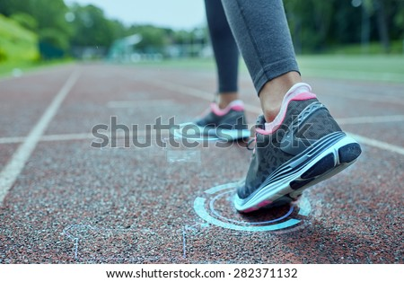 fitness, sport, training, people and lifestyle concept - close up of woman feet running on track from back with futuristic holograms - stock photo