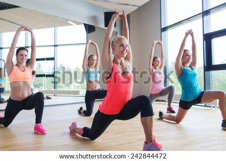 fitness, sport, training, people and lifestyle concept - group of women making lunge exercise in gym - stock photo