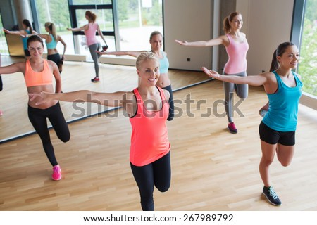 fitness, sport, training, people and lifestyle concept - group of women stretching leg in gym