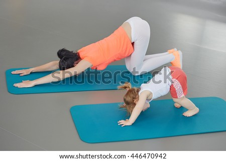 fitness, sport, training, teamwork and lifestyle concept - smiling woman doing stretching on the flore with baby in gym - stock photo