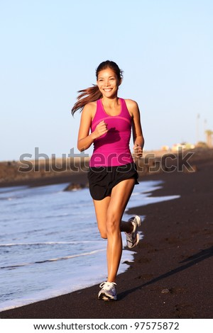 Fitness sport woman running on beach outside at sunset. Healthy lifestyle image of beautiful young asian woman jogging on black sand beach. - stock photo