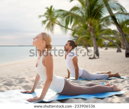 fitness, sport, yoga, people and lifestyle concept - happy couple making yoga exercises on tropical beach - stock photo