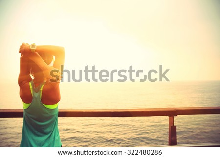 fitness sports woman runner stretching on wooden boardwalk seaside - stock photo