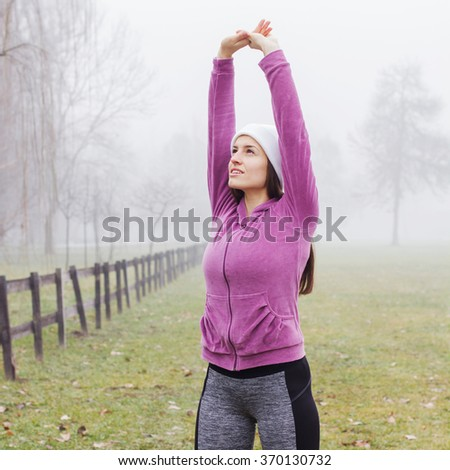 Fitness Sporty Woman, healthy lifestyle concept, stretching exercising, outdoor activity , winter season - stock photo