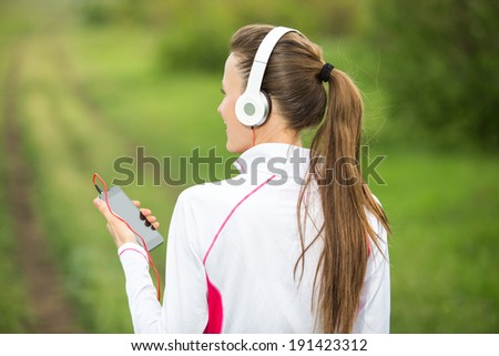 Fitness sporty woman runner running in rural nature listening to music - stock photo