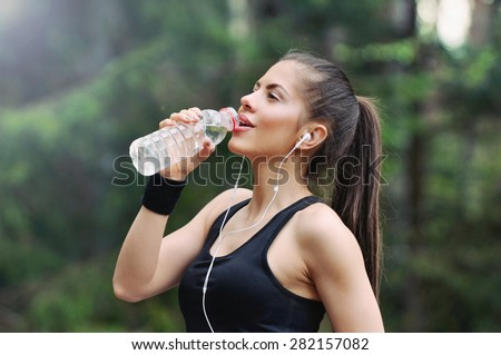 fitness sporty woman running early in the morning in forest area, healthy lifestyle concept - stock photo